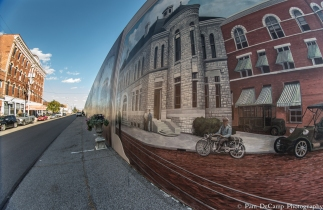 The motorcycle appears to be riding out of the mural